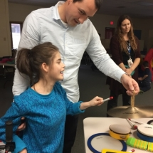 Oak Park Elementary teacher, Zach Lapointe, assists one of his students during a Winter Art Escapes class through Traverse Bay Area Intermediate School District